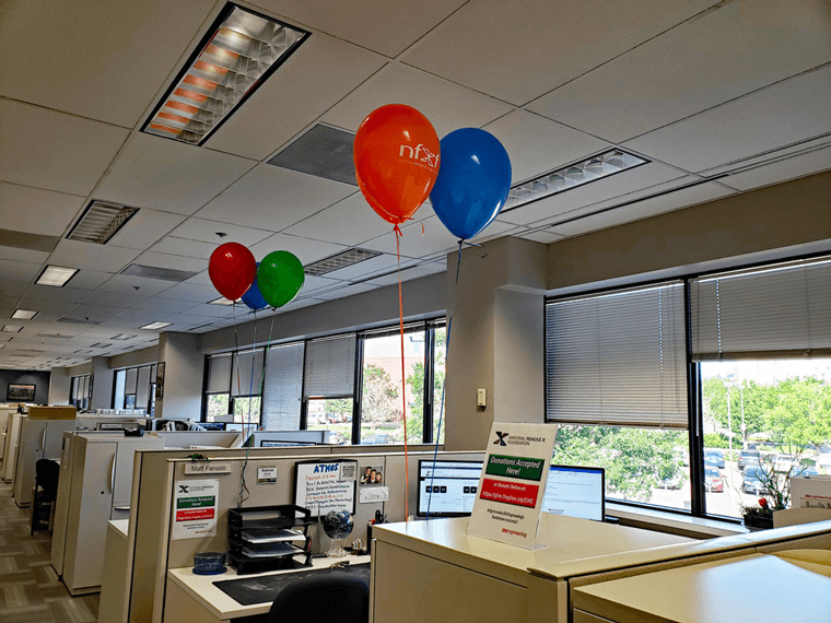 Helium NFXF balloons tethered to cubicle walls and file cabinet