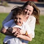 A teen girl holding and playing with a young boy outdoors and laughing