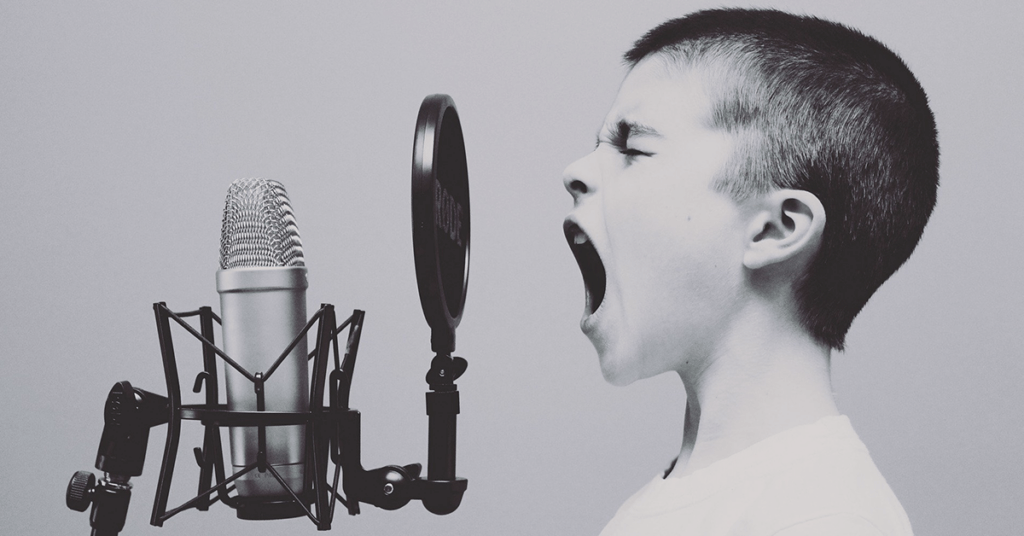 Boy yelling into old-fashioned microphone