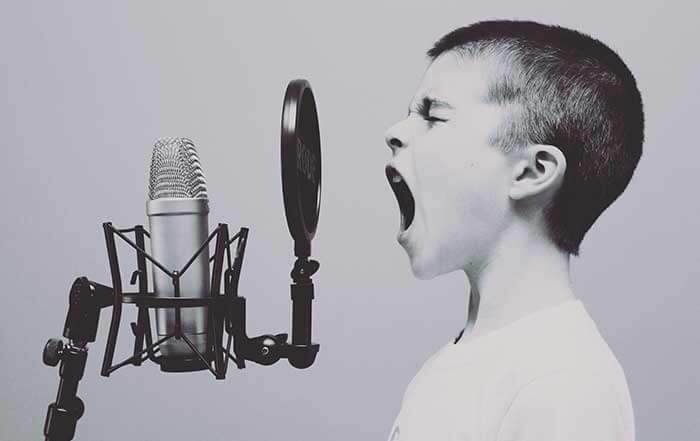 Young boy yelling into microphone