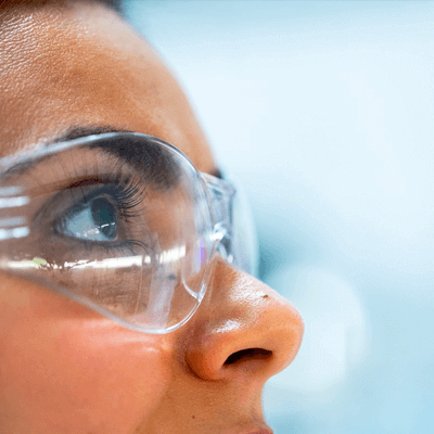 Woman in protective glasses looking to the right and up
