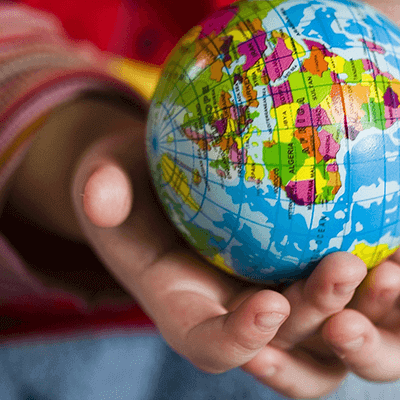 Small child's hands holding toy world globe