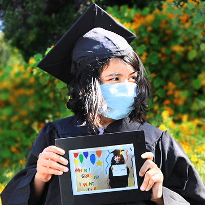 Young girl with Fragile X syndrome wearing graduation hat and robe