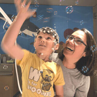 Young male child with sensors attached to his head playing with bubbles in the air while a brunette woman kneels beside him laughing