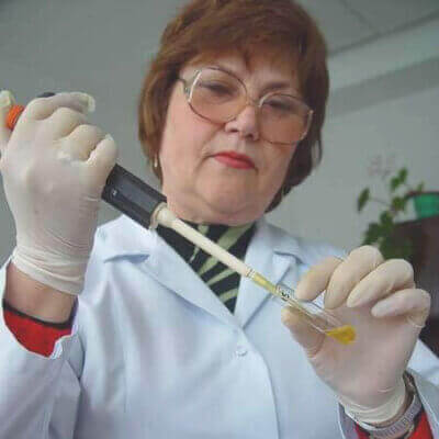 A middle aged short-haired woman wearing octagon frame glasses, a white lab coat, and latex gloves inserting liquid into a test tube