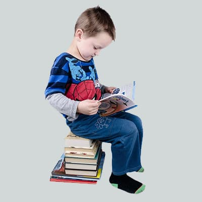 Young boy sitting on stack of books while reading