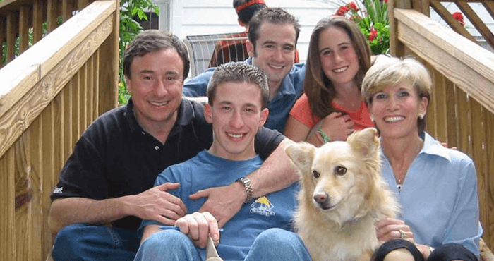 A family and dog outdoors on the steps up to their deck.