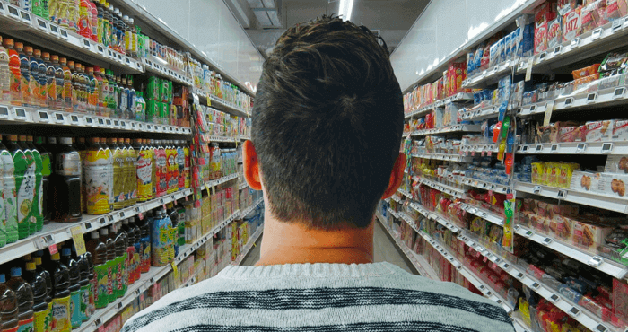 Young man looking down a long grocery store aisle.