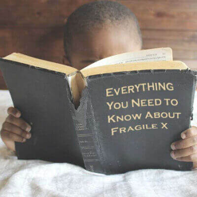 An African-American male toddler in bed reading Everything You Need to Know About Fragile X