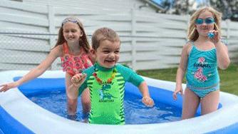 Three children in a kiddie pool
