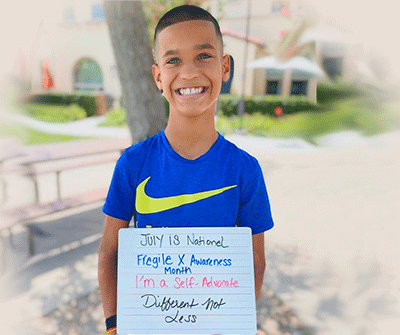 Audric holding a sign reading: July is National Fragile X Awareness Month. I'm a self-advocate. Different not less.