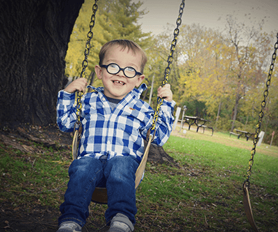 Young boy on a tree swing wearing glasses, plaid shirt, and jeans