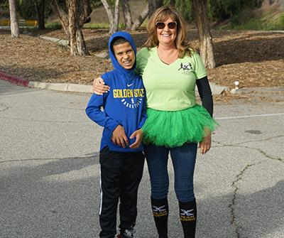 Carole Sperber wearing a green tutu, posing with her grandson Audric