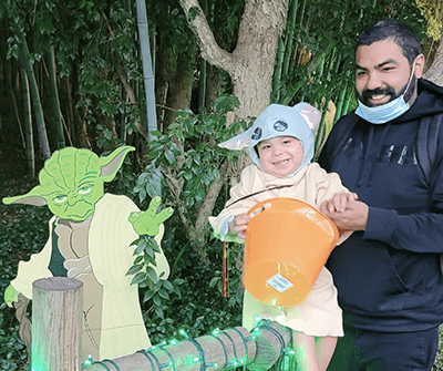Nathanael and son in a Halloween costume and cartoon Yoda