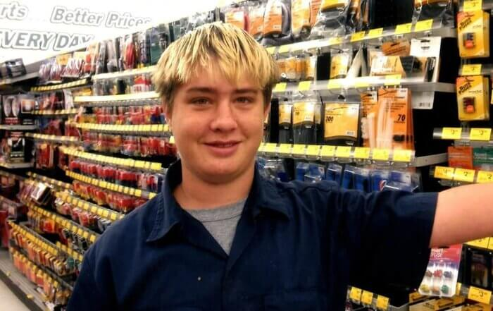 A blonde male young adult working at an auto parts store