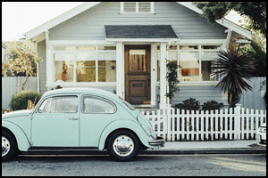 Light blue house with white picket fence and Volkswagon Beetle in front.