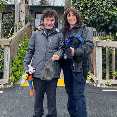 Zach and his mom standing in front of the Monterey Zoo entrance gate